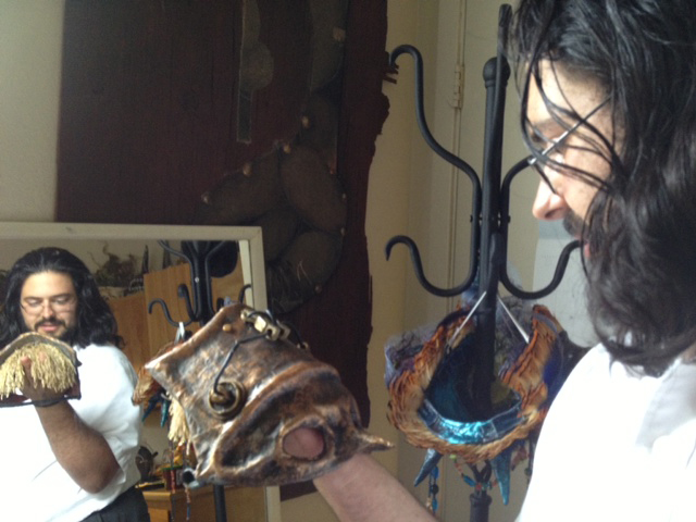 man looks at a mask reflected in a mirror