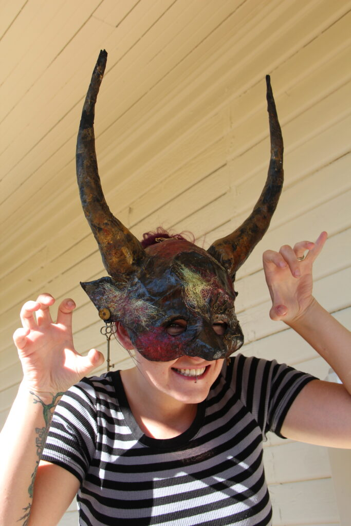 woman poses in a devil mask